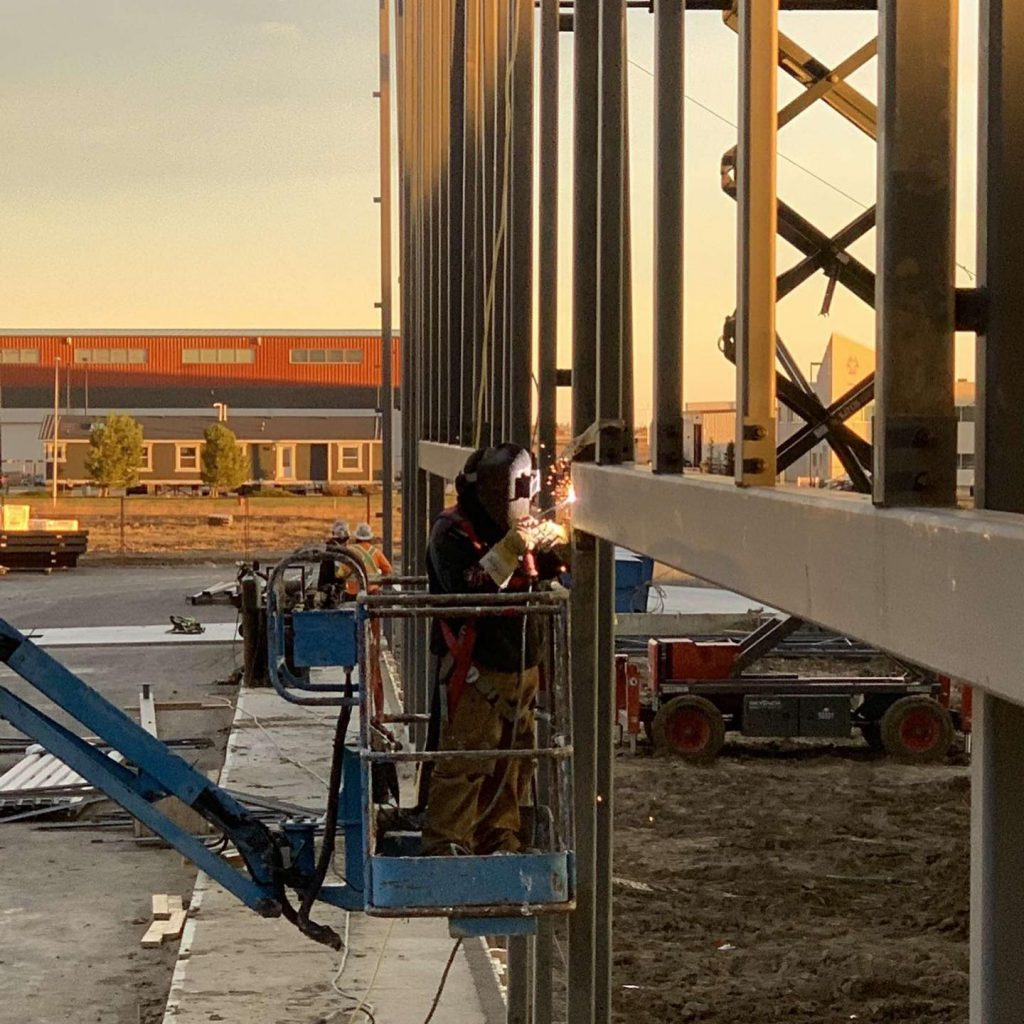One of our Iron Workers Welding a building in a boom.